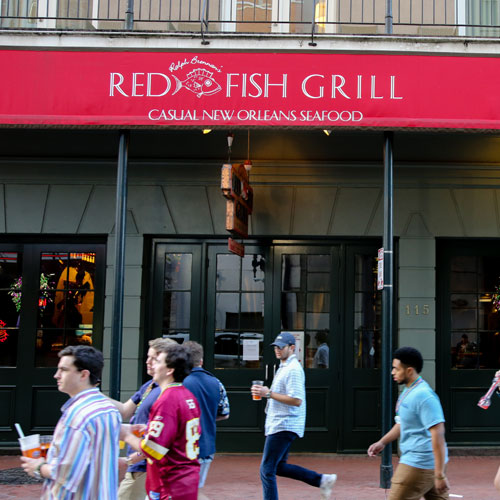 Tourists walking in front of the entrance to Red Fish Grill on Bourbon Street
