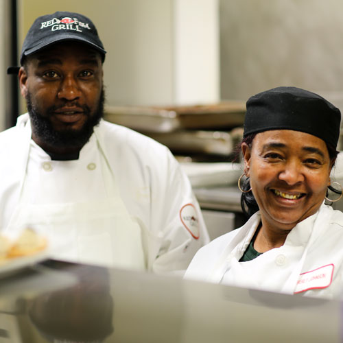 Two kitchen employees smiling for the camera