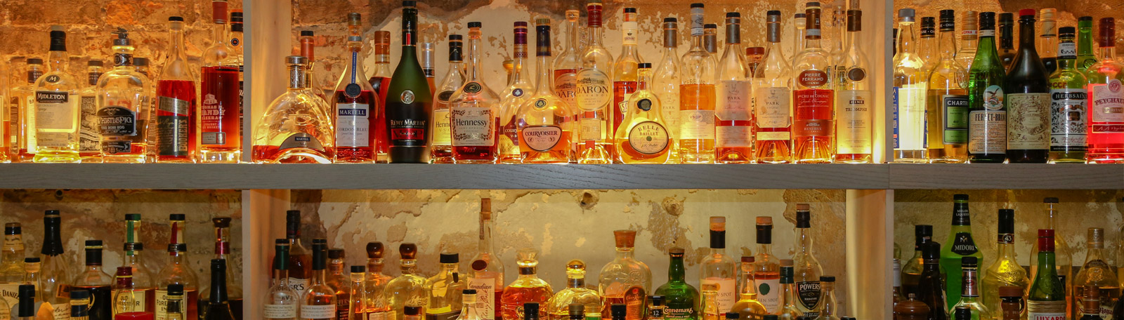 Line of premium quality liquor bottles along the wall behind the bar at the Oyster Bar.