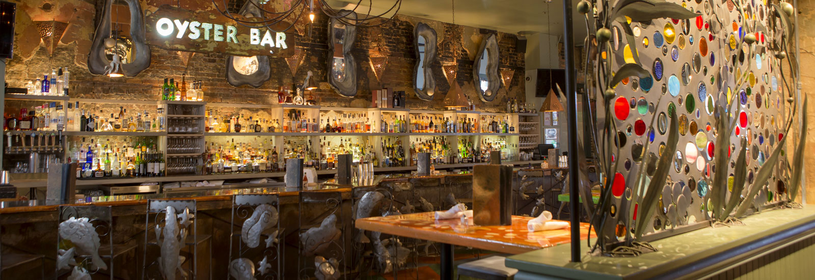 The Oyster Bar at Red Fish Grill shown with alligator barstools and oyster themed mirrors along the wall
